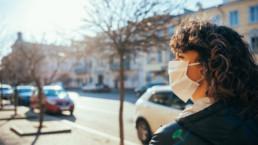 Mujer paseando por la calle con mascarilla COVID-19