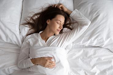 Mujer durmiendo bien en su cama - Vida saludable