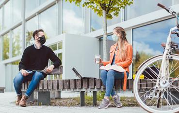 Dos personas hablando con mascarillas en un parque Covid-19