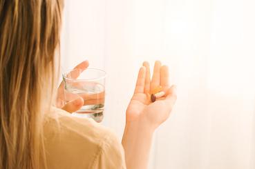 Mujer tomándose un suplemento de Vitamina D en pastillas con agua