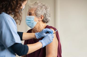 Mujer mayor de 65 años siendo vacunada contra el COVID-19