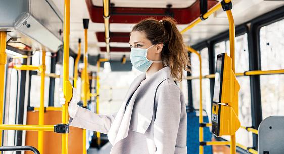 Mujer protegiéndose con mascarilla del COVID-19 en el autobús