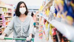 Mujer con mascarilla comprando comida en un supermercado