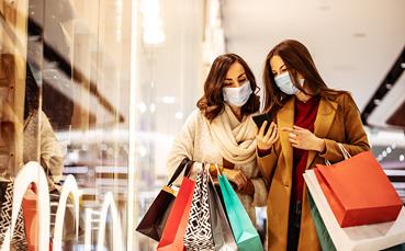 Mujeres con mascarilla comprando ropa en una tienda