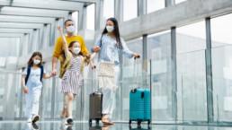Familia manteniendo el distanciamiento contra el COVID-19 en el aeropuerto