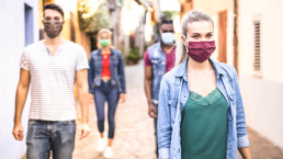 Jóvenes andando por la calle con mascarilla