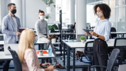 Personas en la oficina, siguiendo las normas de prevencion COVID-19
