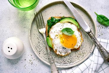 Tostada integral con aguacate, espinacas y huevo.