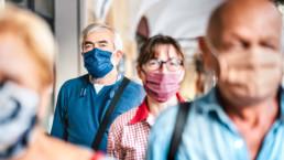 Grupo de personas utilizando mascarilla en el exterior para evitar la propagación de la COVID 19
