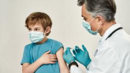 Niño siendo vacunado de la COVID-19 por médico