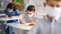 Niños con mascarilla covid en clase.