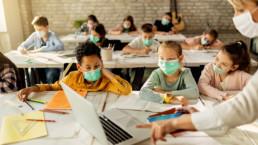 Niños estudiando en clase con la profesora ¿están protegidos contra la COVID19?