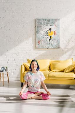 Mujer meditando en su casa.